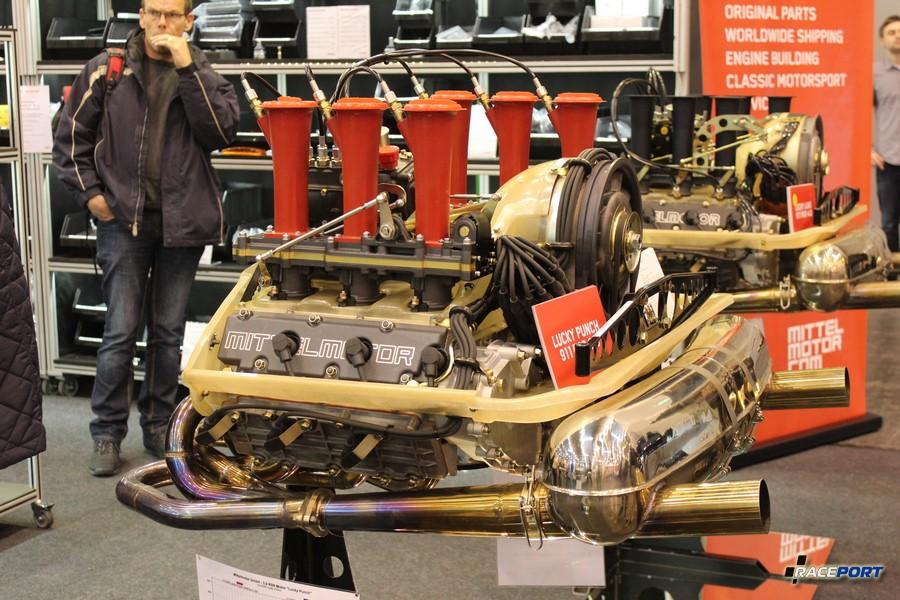 Загляденье стенд с двигателями Porsche. На висящей табличке модель и график с мощностного стенда