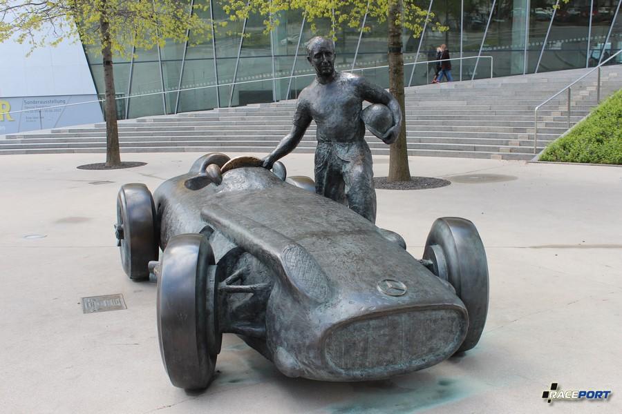Перед входом красуется памятник серебряной стрелы W196 R и Juan Manuel Fangio затертый до блеска детьми. (инсталяция мая 2006 г.)